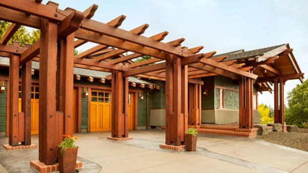 A series of redwood trellises creates a period-style pergola to screen the garage, which has new doors of cedar.