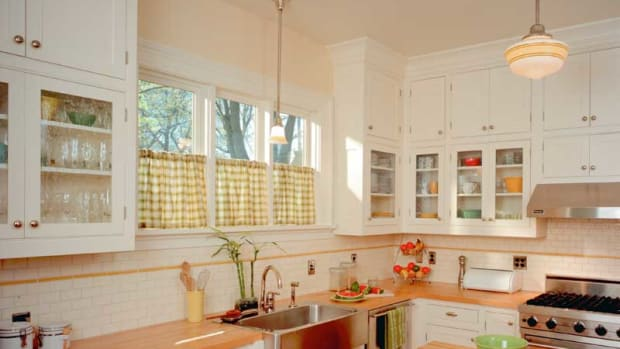 Period conventions include wood countertops with white paint and schoolhouse lights. Photo: William Wright