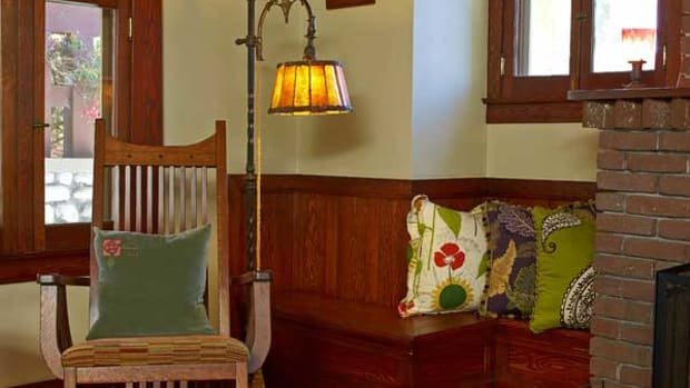 In the living room, a historical revival, Art Deco-era floor lamp has an unusual rope mechanism to lift and lower the shade. Pillows with botanical motifs and vivid colors soften the Craftsman woodwork.