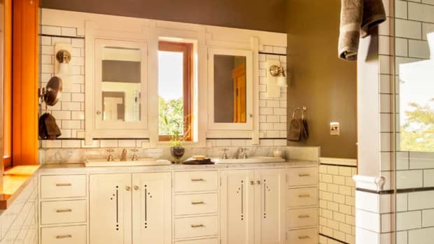 The master bathroom is part of a comfortable suite. Dark walls set off the creamy tile and cabinets.