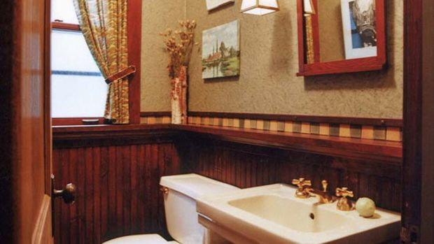 This Chicago bath has a historical feel done up in a dark wood wainscot and checkerboard floor. Art and mirror hang from a picture molding, a nice detail. Greene & Proppe Design. Photo by Christopher Lark.