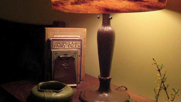 Reverse-painted scenic Handel lamp with a Grueby vase and Roycroft trillium bookends.