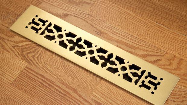Scrollwork-pattern heat register in brass finish by Reggio Register.