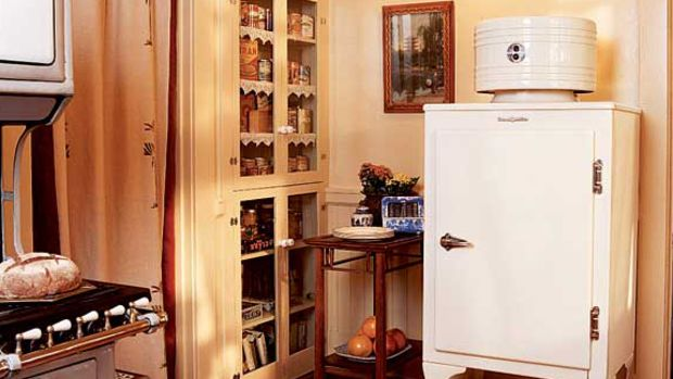 Near the monitor-top fridge, a portiere masks the door opening that leads to a dark hallway; the homeowner stenciled the rough linen fabric.
