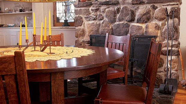 A Gustav Stickley dining table and 16 matching chairs are lit by a Tiffany fixture. As in Stickley's own home, the furnishings and architectural materials such as the stone fireplace are the décor; there is no applied decoration.