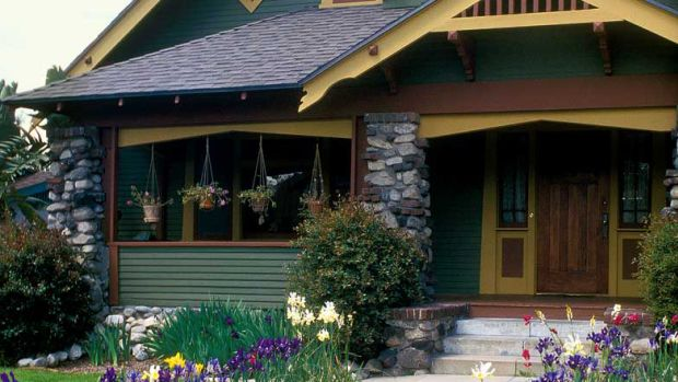 Trimwork includes a gable truss on brackets, bargeboards, and exposed rafter tails under the porch roof. Photo: Doug Keister