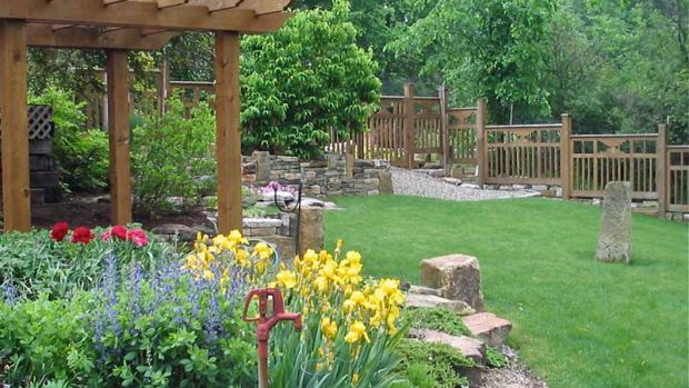A cedar pergola over a path and a cedar fence divide garden in Ohio.
