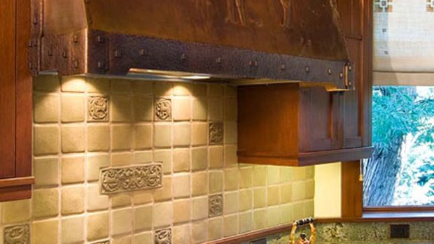 The 200-pound copper range hood is by Joseph Mross of Archive Designs. A deer theme continues on custom-made tiles by Laird Plumleigh.
