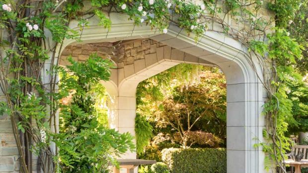 Climbing roses soften a stone arch. Photos: William Wright