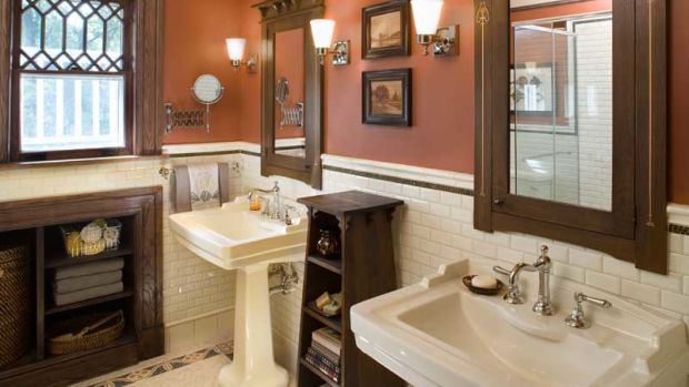 While oak trim and off-white subway tile are standard in many Arts & Crafts baths, this one gains depth from terra-cotta walls and the artful use of borders and inlays.