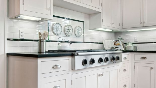 Cabinets, finishes, tile, lighting, and hardware all nod to the period. Photos by Larny Mack