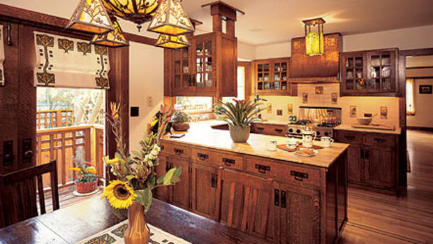 Elements of the revival kitchen: an antique chandelier; reproduction textiles (from Arts & Crafts Period Textiles); hardwood cabinets; art tile.