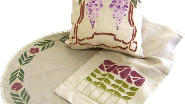 The stenciled pillow, table topper, and table runner are by Ann Wallace.