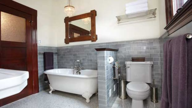 A pony wall separates the new clawfoot tub from the toilet. The framed mirror dates to 1912.  All photos by Mats Bodin