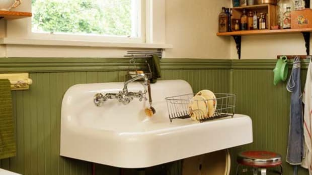 A wall-mounted sink, purchased in barely used condition, replaced the ruined 1970s sink and particleboard base cabinet. The faucet is a reproduction. The design of simple fir shelves on iron wall brackets was inspired by a vintage photograph.