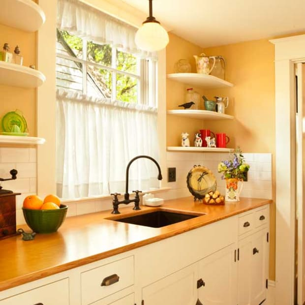 """In the pantry, wood countertops surround a copper sink. A dishwasher is hidden behind false drawer fronts. The """"flipper doors"""" under the sink add a period touch."""