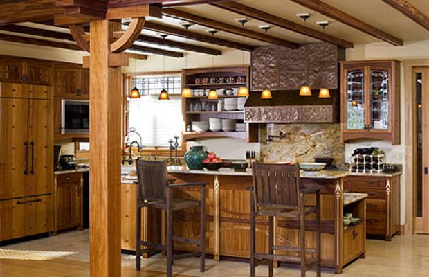 Tucked into a corner, the kitchen is separated from the living room by an embellished pier and the back of the island. The pantry cabinet is off to the right.