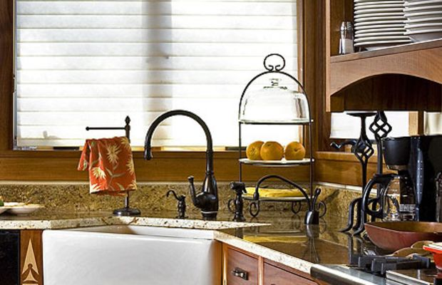 The large, apron-front sink is in the corner beyond the stove. Note the restrained leaded-glass pattern in the Andersen windows.
