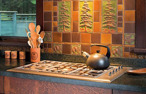 In an Arts & Crafts Revival kitchen, an artistic tile panel by Handcraft Tile Co. and oak cabinets lend appeal to a kitchen with modern appliances. Photo by William Wright.