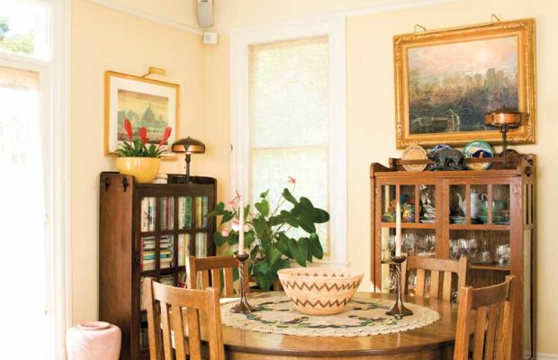 In a 1906 California bungalow, the dining room is furnished with antique oak pieces and plein-air paintings, Native American baskets, and a bowl chandelier by Michael Adams of Aurora Studios. Photo: William Wright