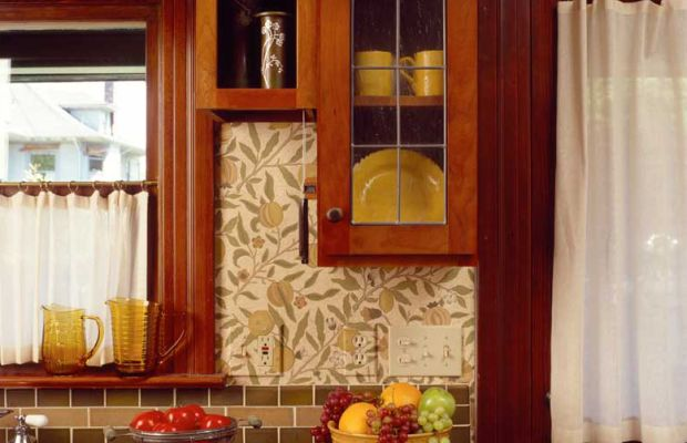 Earthy tiles, Morris wallpaper, and warm cabinets come together in a revival kitchen.
