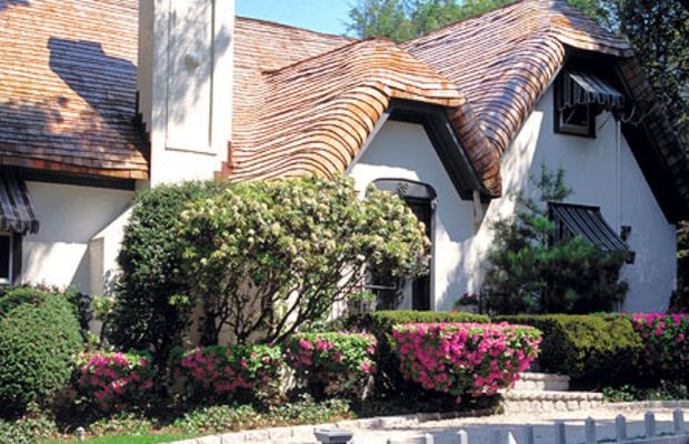 """An English cottage with new shingle """"thatch"""" roof by Custom Cedar Solutions."""