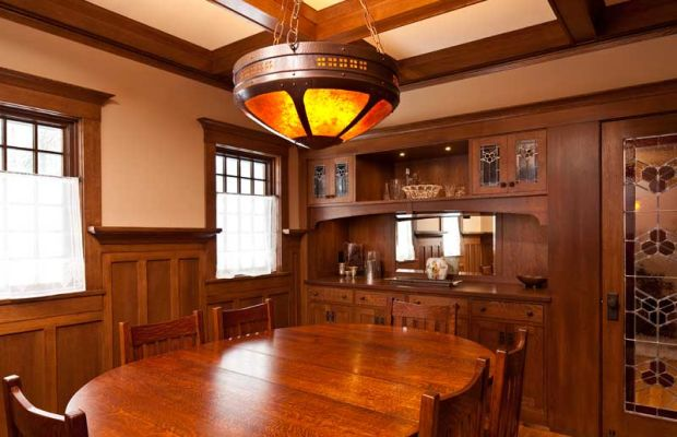 The beamed dining room has a large, six-panel, up-lit mica fixture made by James K. Davies of Craftsman Copper. The built-in sideboard is typical of Arts & Crafts houses. Leaded art glass has a trefoil motif that repeats throughout the house.
