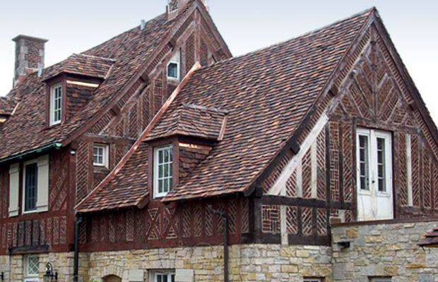 Clay roof tiles newly laid on a half-timbered manse, by Tile Roofs, Inc.