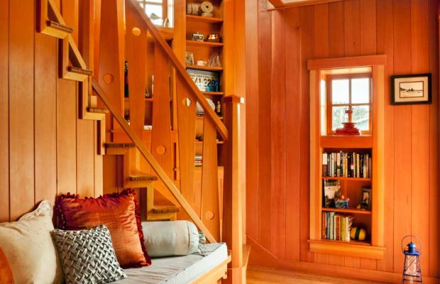 A built-in bench with storage tucks into the tower staircase. Tower windows crown bookcases.