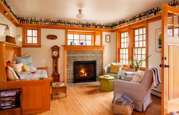 A collection of beer bottles rings the vacation cabin's living room, where a space-saving, built-in settle was designed to include a roll-out trundle bed. A border of glass tiles is a beachy note in the surround facing the gas fireplace.