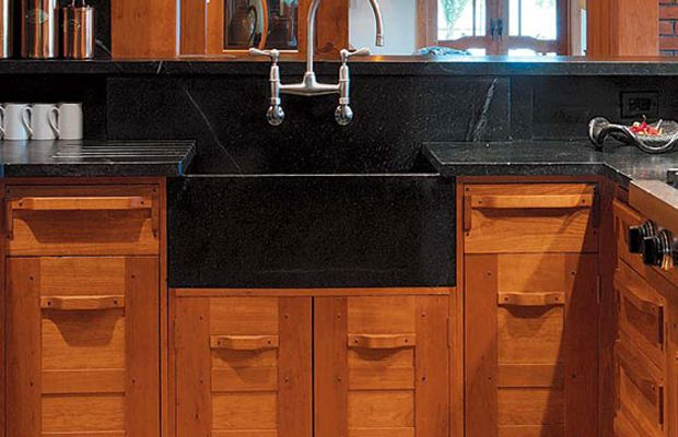 Dark stone is often used in today's revival kitchens; here it is paired not with white tile and cabinets, but rather with natural-finish woodwork reminiscent of California architects Greene & Greene. Photo by Carolyn Bates.