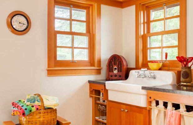 The family asked for an old-fashioned kitchen evoking the 1920s—complete with fabric skirts. The circular cutouts featured in staircase balusters are repeated in kitchen cabinets.