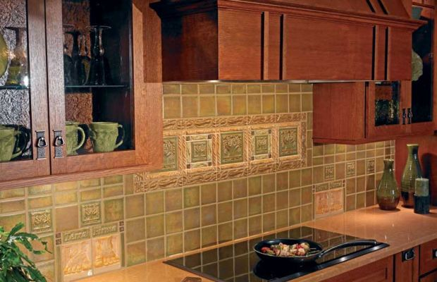 A kitchen backsplash incorporates whimsical pairs of sculpted 'Foot' tiles and Terra Firma's theme tile, 'Tree of Life'.