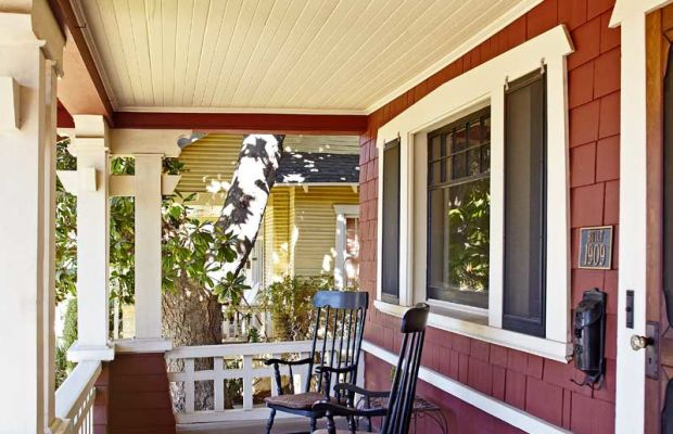 From the full-width porch, the owners and neighbors can appreciate the original trim, triple window, and front door.