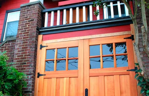 Garage space is tucked between brick piers underneath a porch. The open-swing new doors work in this case, and their Craftsman design pulls the facade together. Photo courtesy Real Carriage Door Company.