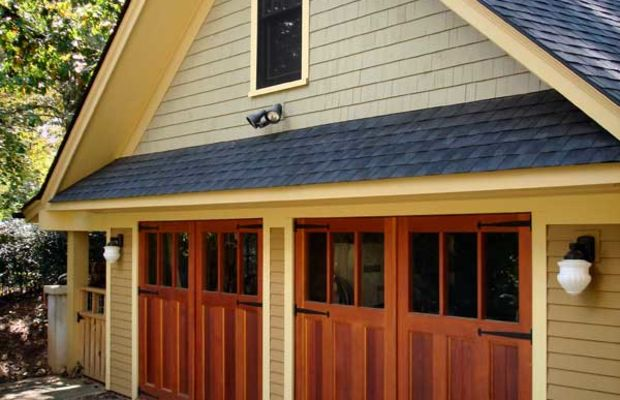The new garage for a 1902 Shingle Style house in North Carolina has custom-made doors in an Arts & Crafts three-panel pattern. Double-hung windows match the ones on the house. Photo courtesy Mathews Architecture.