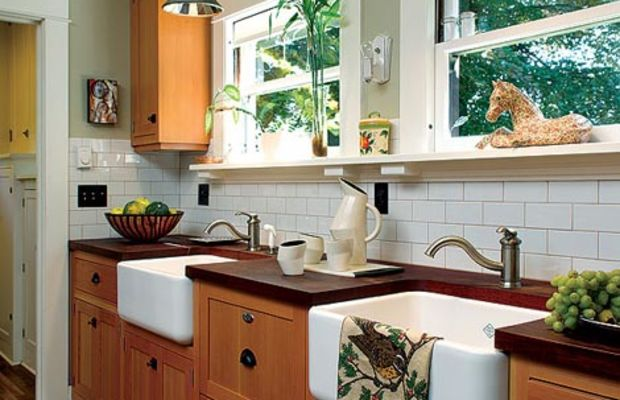 Fir cabinets join mahogany countertops and a backsplash of subway tiles. A pair of farmhouse sinks was installed under the windows with a dishwasher hidden in between.