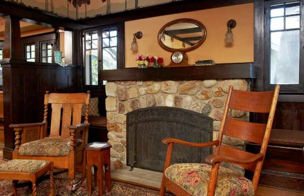 A stone fireplace anchors the chimney end of the living room.