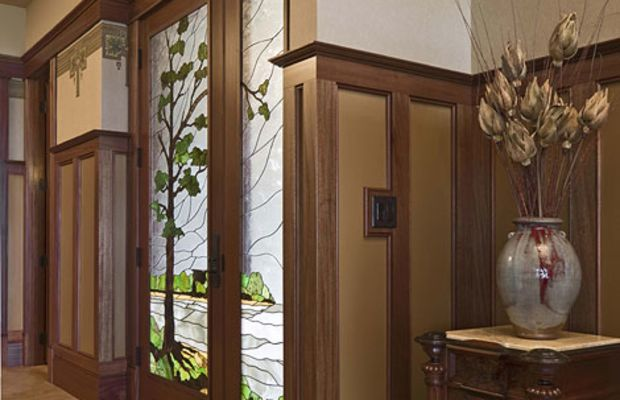Custom home-builders Mike and Susan Hoien created a house of timeless design for themselves in Iowa. The entry features custom art glass with an oak-tree motif.