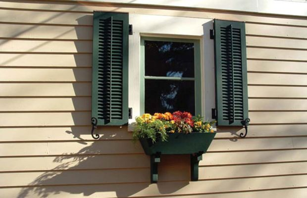 Louvered shutters allow ventilation even when they are closed. Note the S-shaped shutter dogs that hold them open.