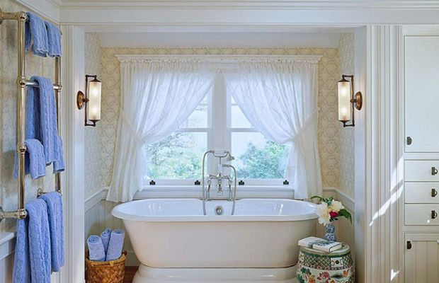 Period-friendly, well-furnished details include wallpaper, a Roman pedestal tub, and built-in storage. Photo by Brian Vanden Brink.