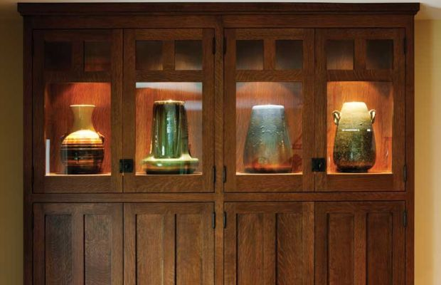 An end cabinet has lighted display space for special pieces of Fulper pottery.