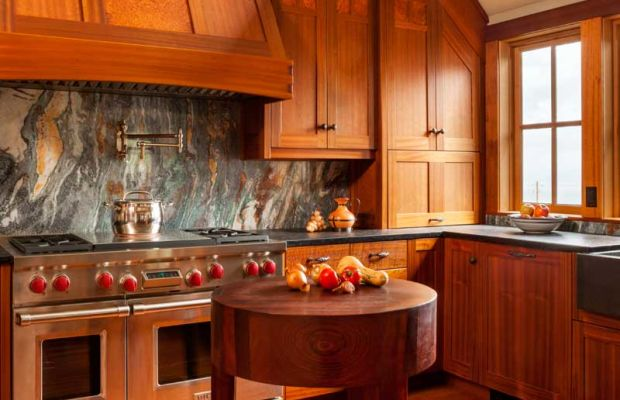 Builder Overbay handcrafted the stove hood and the three-legged chopping block. Countertops are black granite with an antiqued finish; the backsplash is colorful Van Gogh granite.