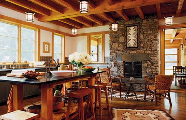 An open floor plan hearkens back to the classic Adirondack lodge. The two-sided fireplace warms both the kitchen and the screened porch.
