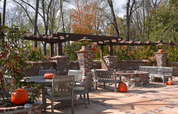 Lit by period-style pier lanterns, the patio includes several dining and seating areas, including one around a rubble-mix fire pit.