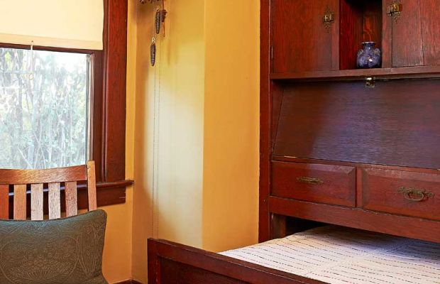 Here's an original: In what may have been the maid's room in this 1909 chalet–bungalow, a built-in, drop-front writing desk disguises the twin hideaway bed that rolls out beneath.