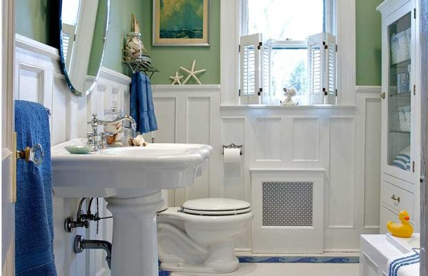 "This ""sanitary"" white bathroom designed by Carisa Mahnken edges toward cottage style with a wood wainscot, extra color, and a  whimsical wave border in the tile floor."