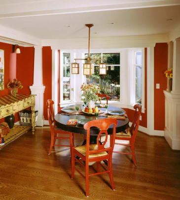 The dining room is a highly colored complement to earthy rooms, grounded by wide-plank oak floorboards with a dark stain.
