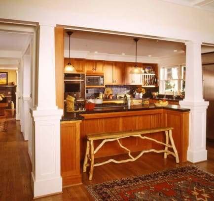 Although open to other rooms, the kitchen is separated by columns and a half-wall with built-in countertop.