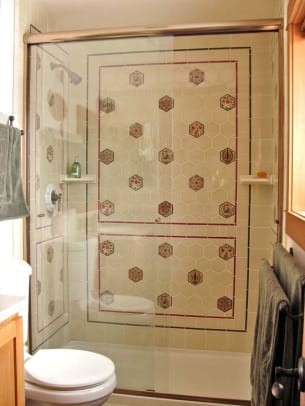 Practical tiles in the shower become an art piece with deco hexagons. Tile by Designs In Tile.